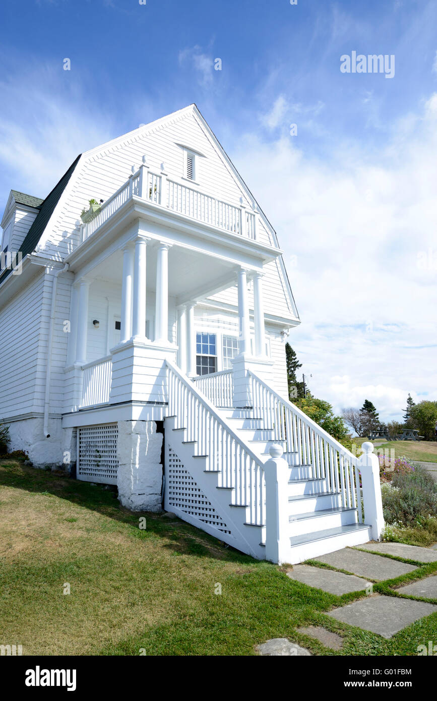 exterior of an old white house on the Maine coast.  The house is white, with steps leading to the front door and Stock Photo