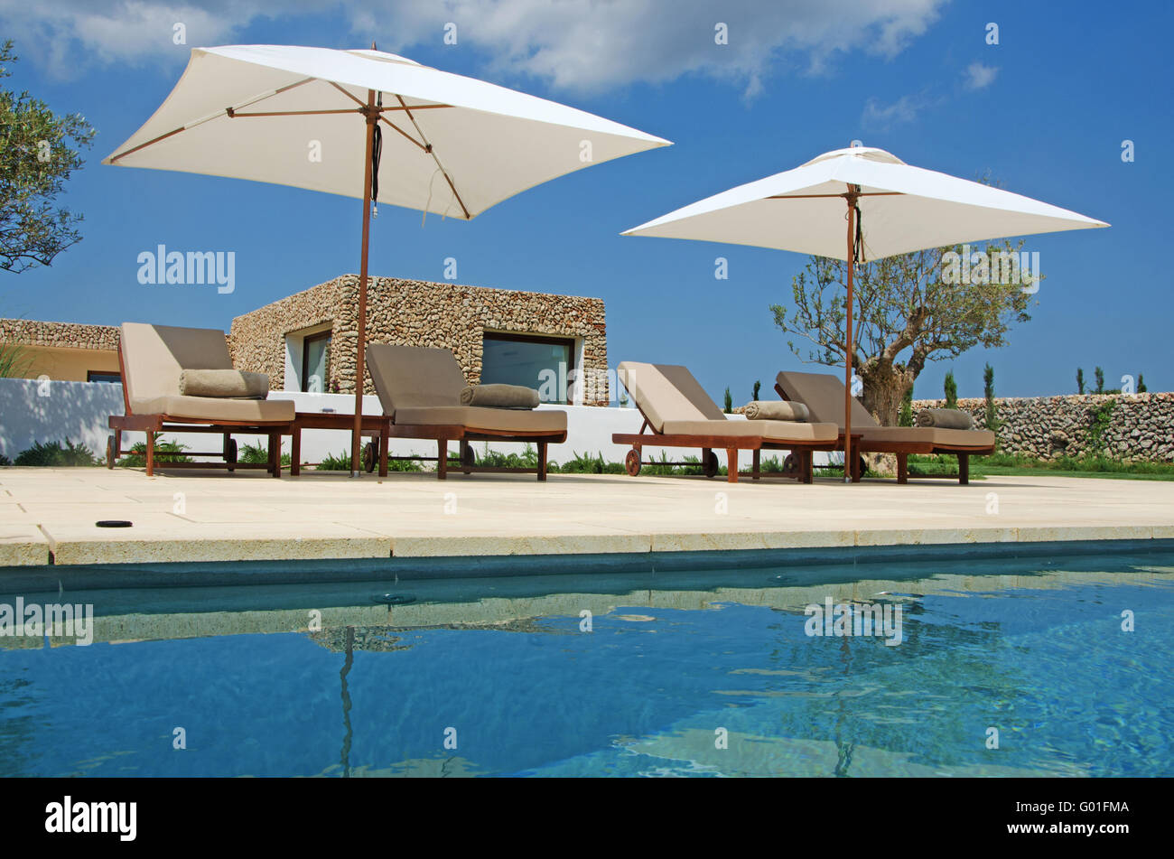 Menorca, Balearic Islands: lawn, pool, olive trees, deckchairs and beach umbrellas in the menorcan countryside - Stock Image