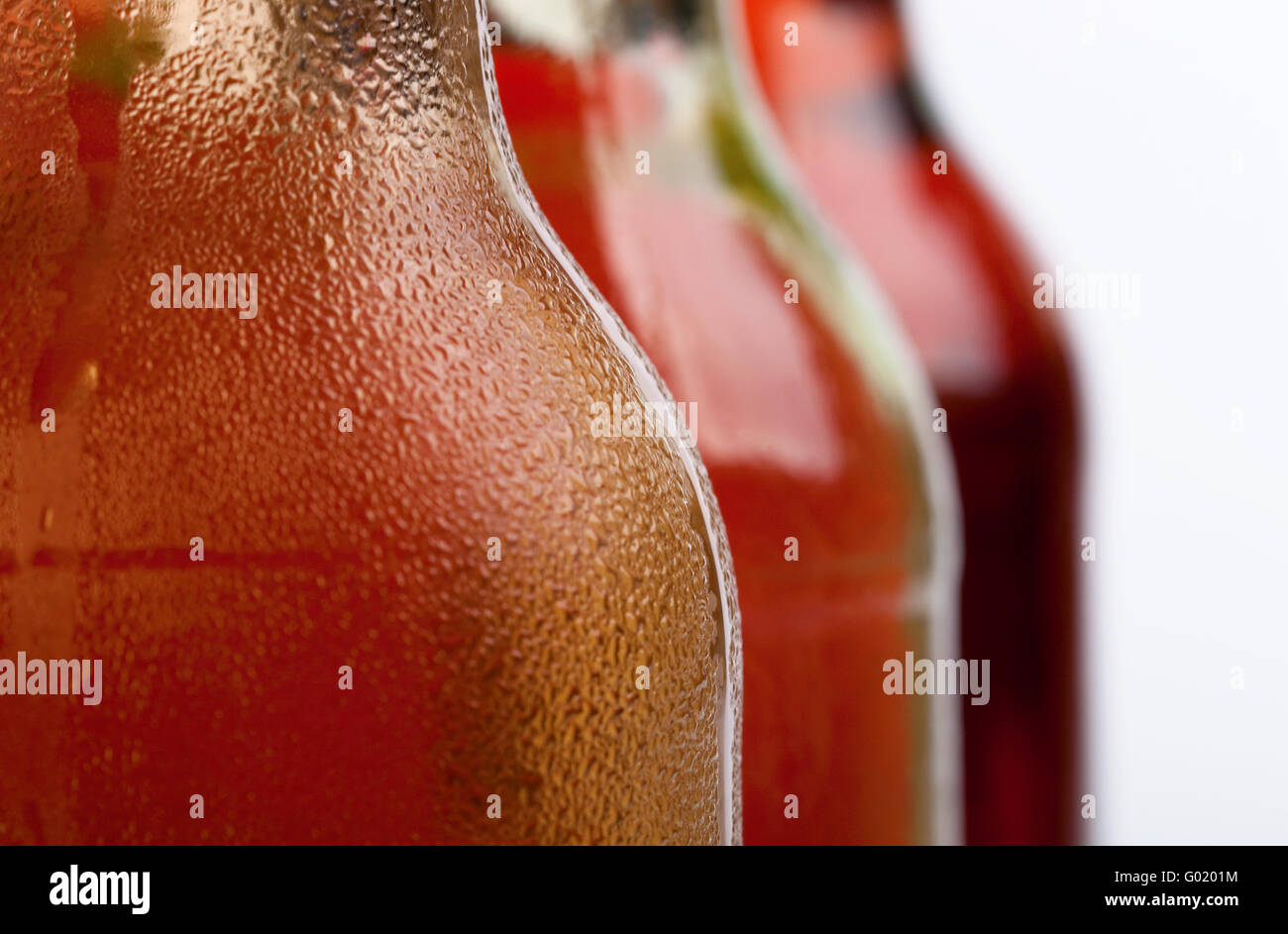 A closeup shot of three cool bottles of fresh beverages - Stock Image
