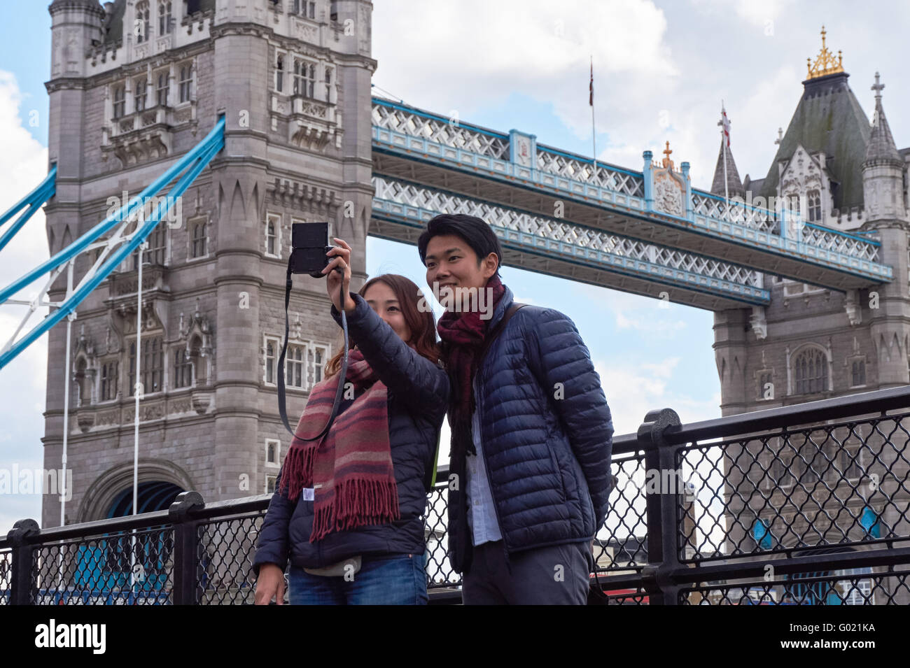Asian tourists taking selfie with Tower Bridge in the background, London England United Kingdom UK Stock Photo