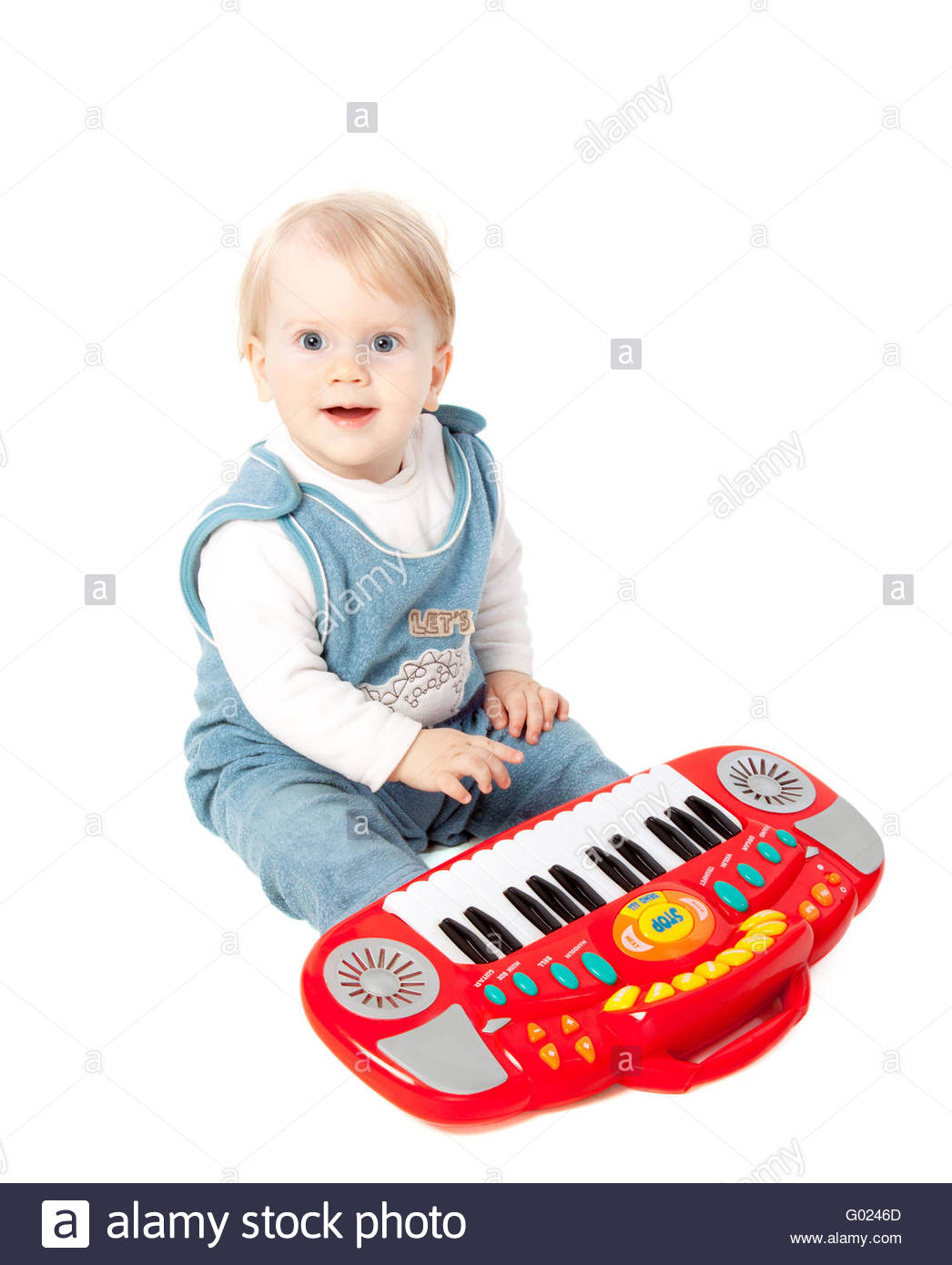 pretty little baby girl pianist plays on a toy piano synthesizer isolated on white - Stock Image