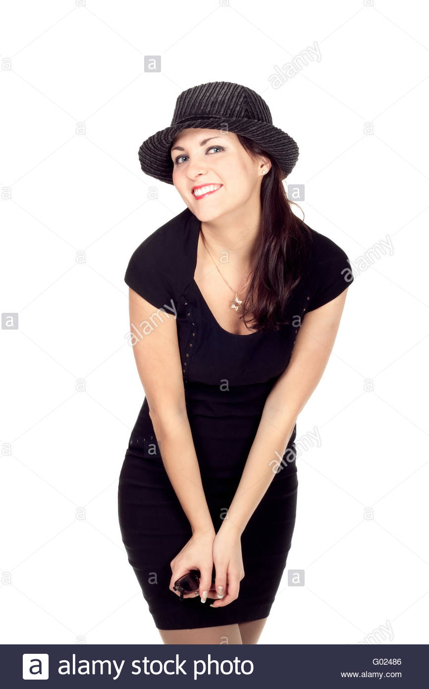 young woman in a hat and a black minidress smiling into the camera isolated on white - Stock Image