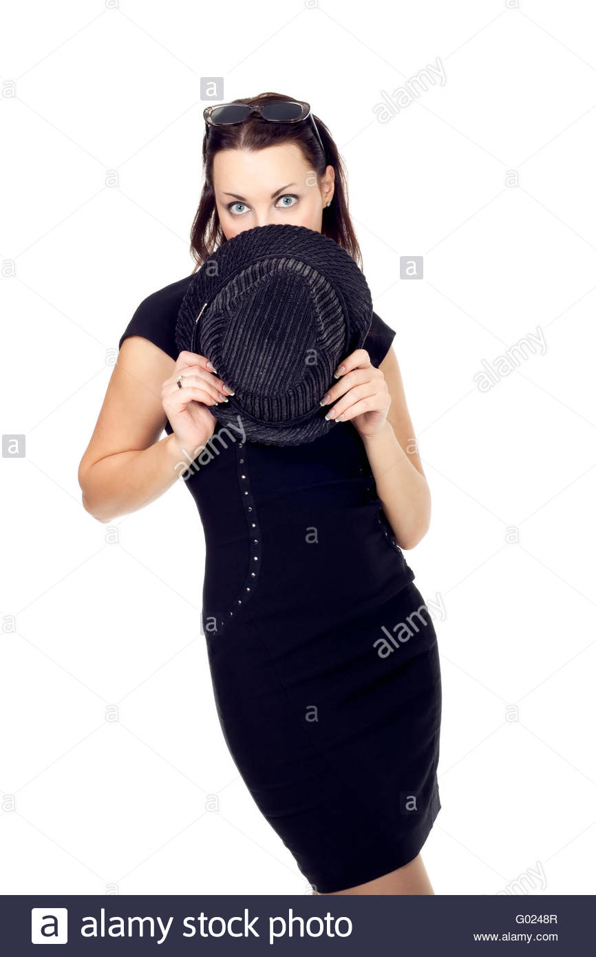 young woman in a black minidress and covered his face with his hat isolated on white - Stock Image