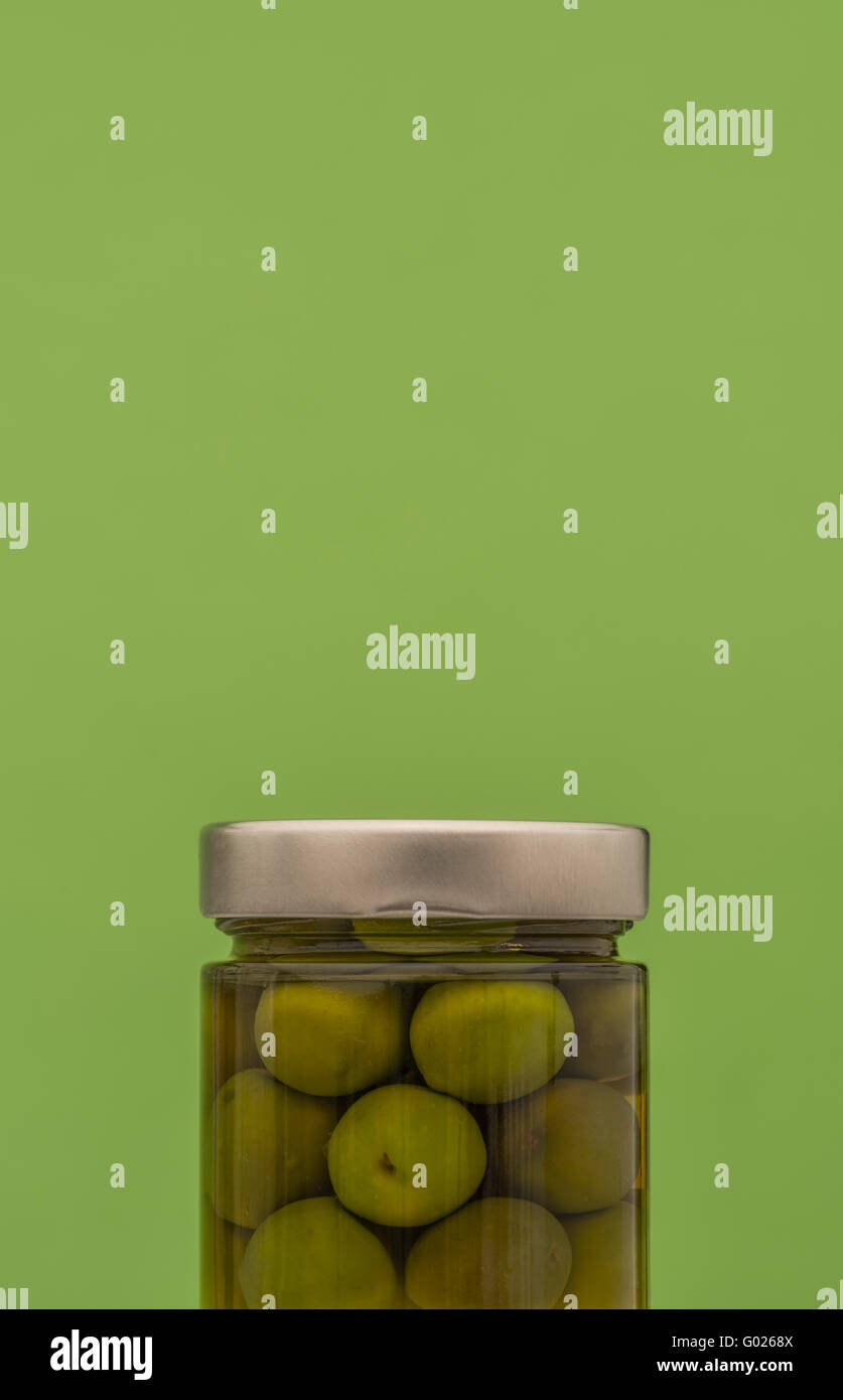 Jar of green olives with silver lid against green background - Stock Image