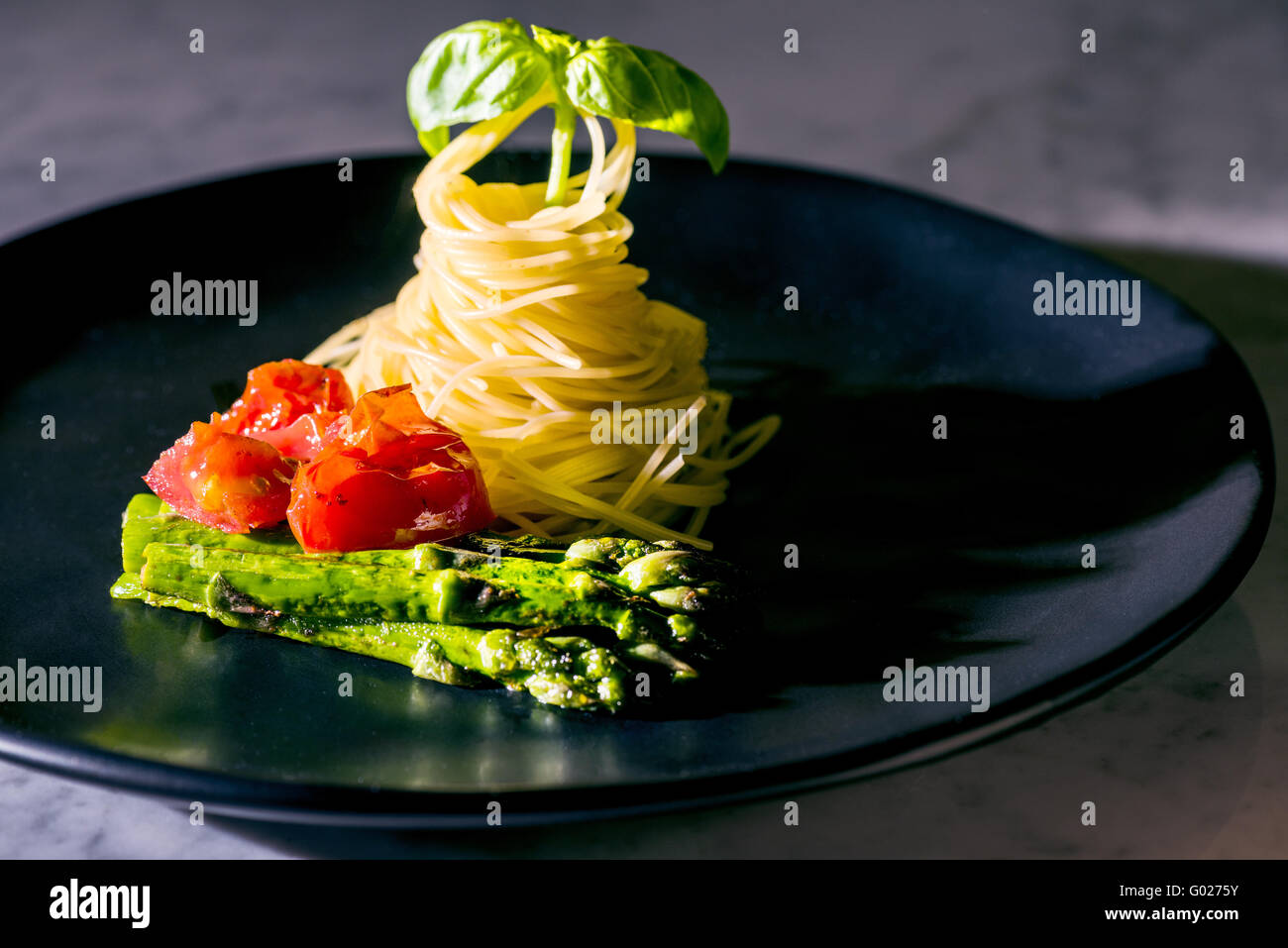 Pasta noodles spaghetti tomatoes basil asparagus on black plate green red black fine food italian italy classy fast - Stock Image