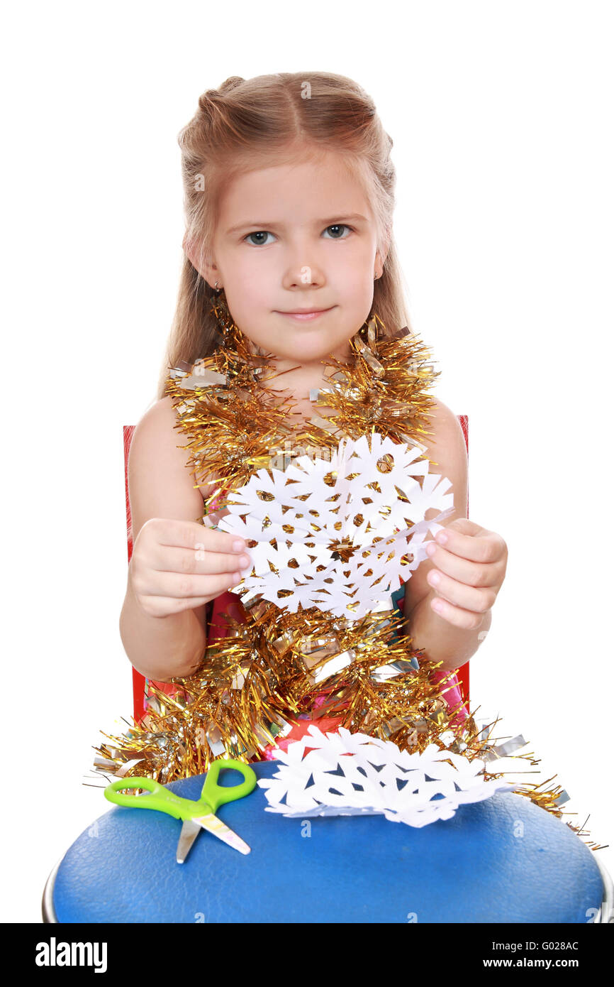 A girl holds a cut out of a paper snowflake Stock Photo