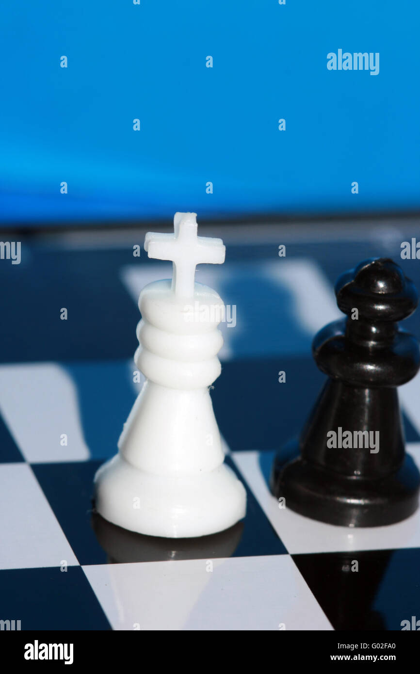 white chess king stands on a chess board with figures - Stock Image