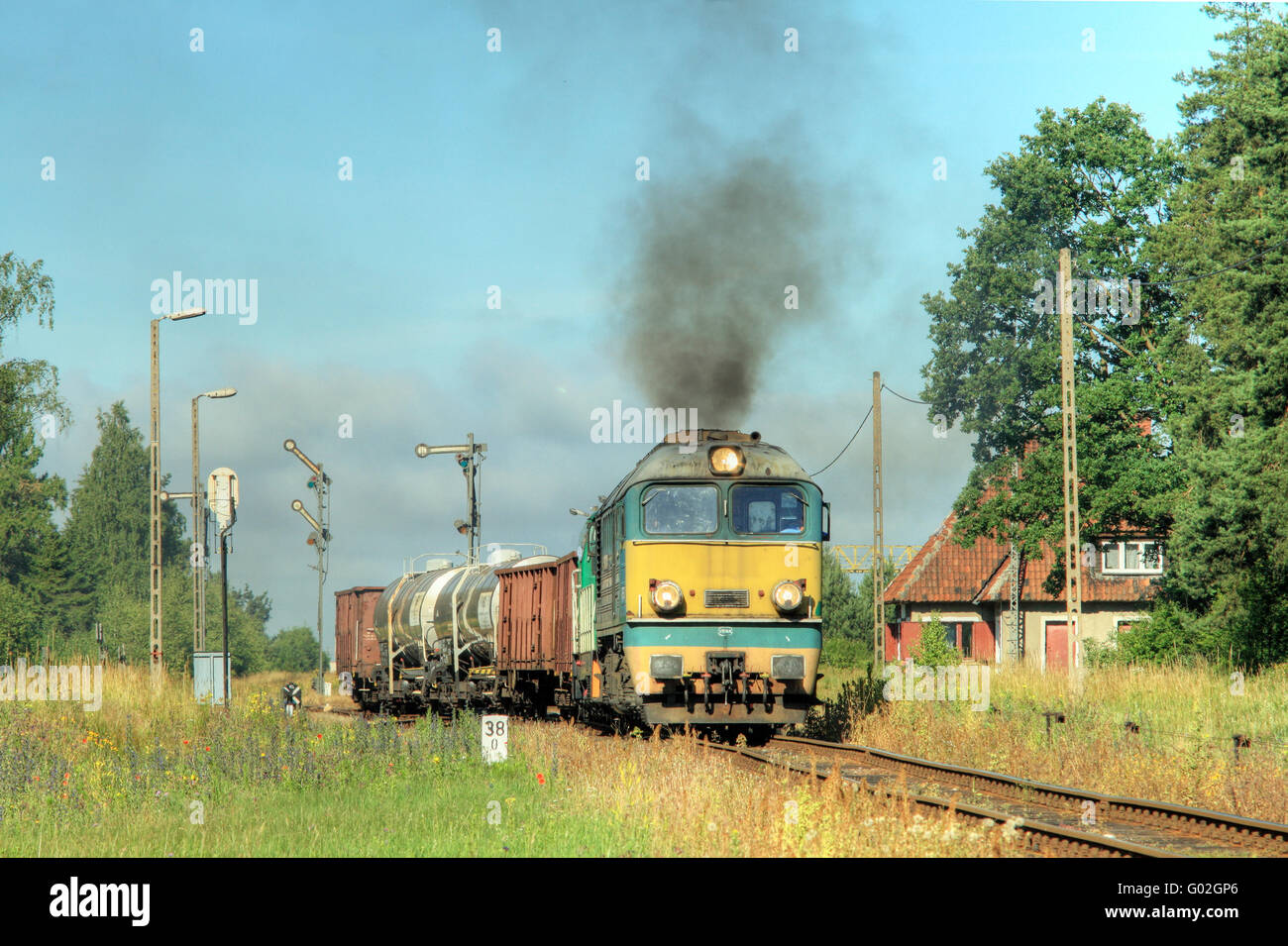 Rural summer landscape with freight train starting from the station - Stock Image