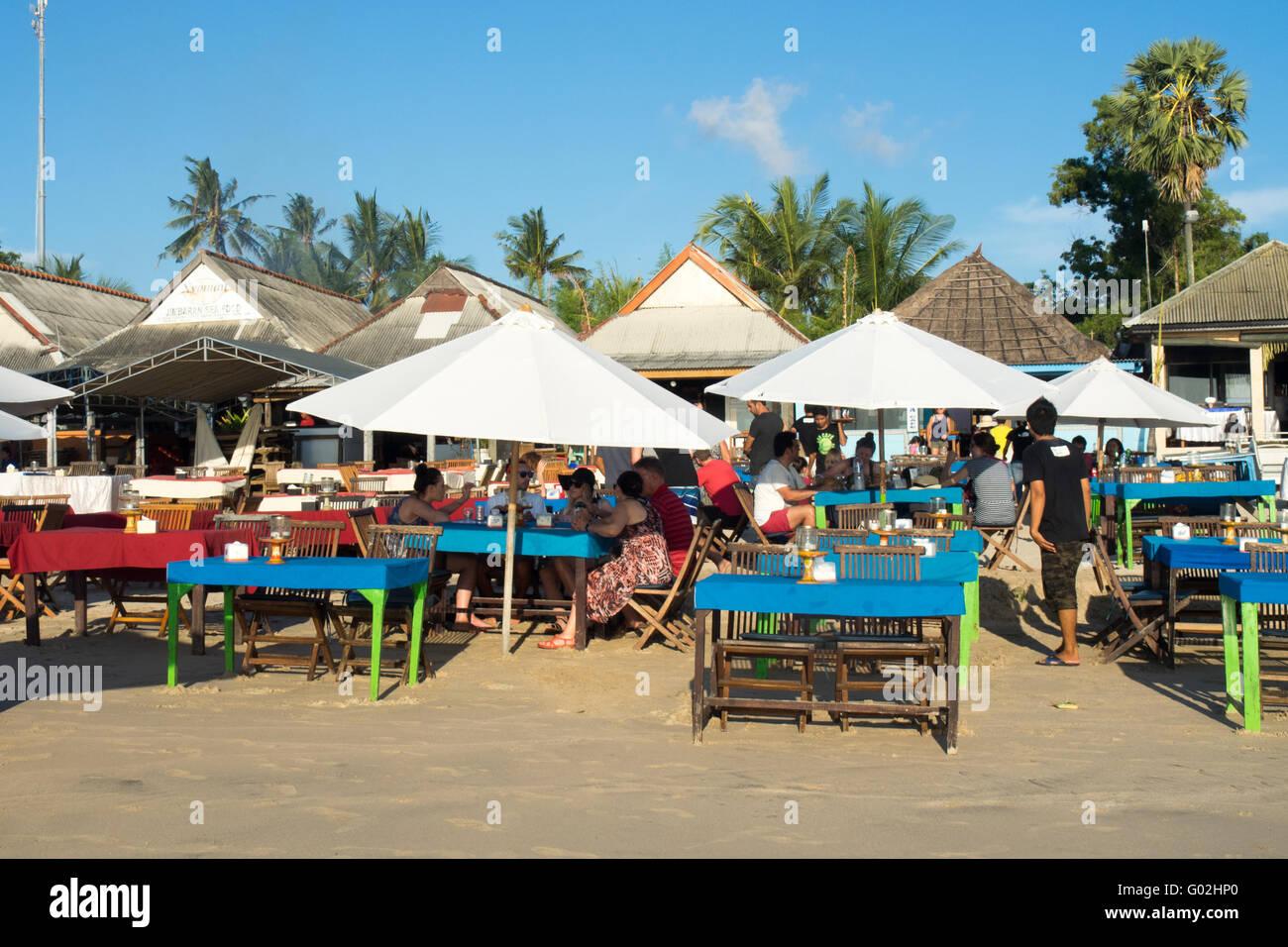 Alfresco dining on the beach at Jimbaran Bay, Bali. - Stock Image