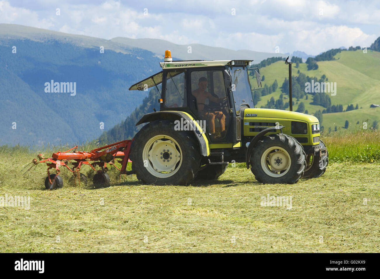 Tractor with hay machine on a Alm - Stock Image