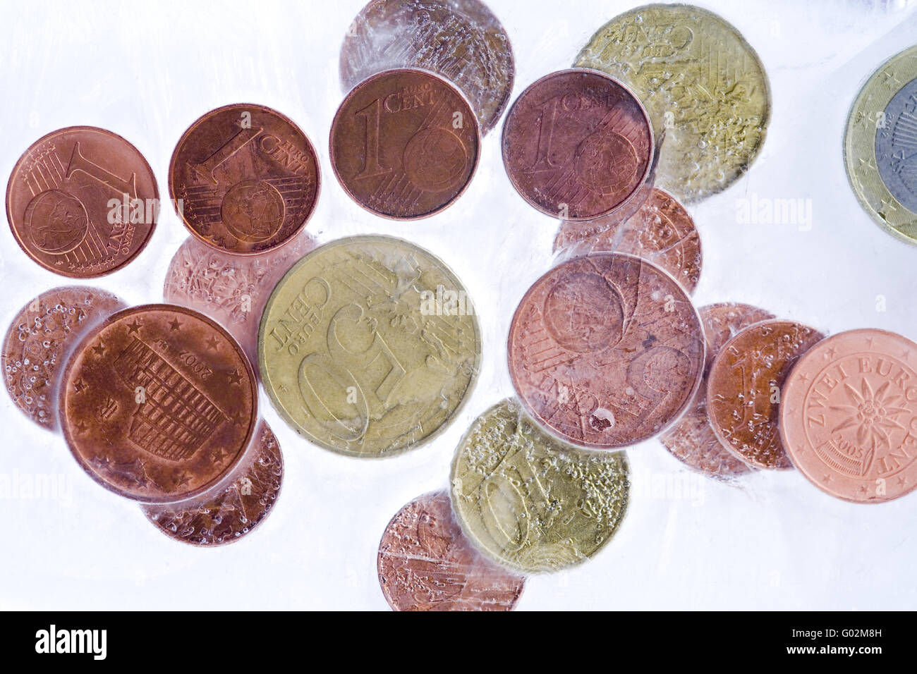 coins in ice - Stock Image