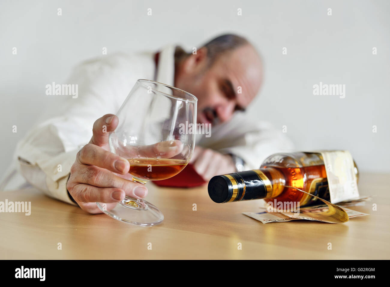 Drunkard sitting with a cognac and a bottle of bra - Stock Image