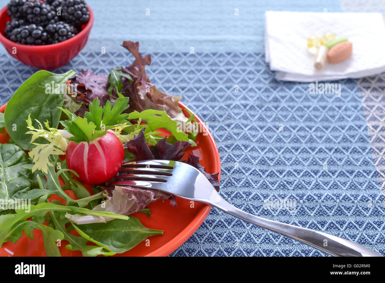Spring mix salad, blackberries, and antioxidant supplements on blue table cloth Stock Photo