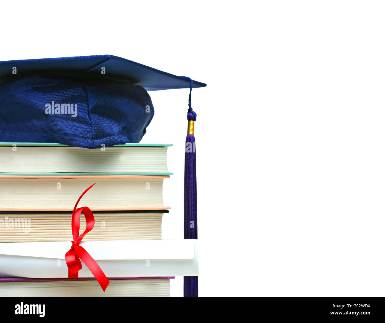 Stack of books with cap and diploma on white - Stock Image