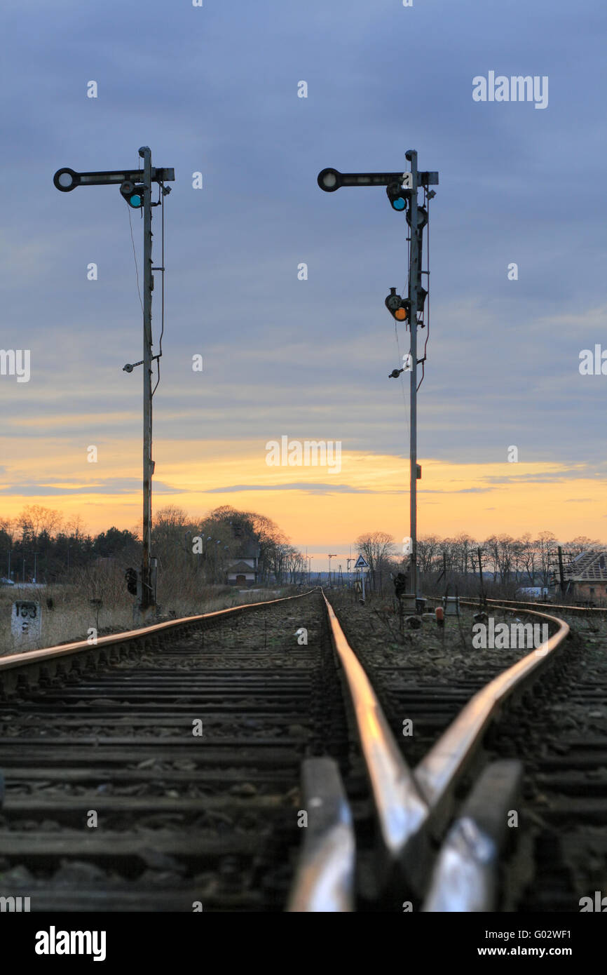 Old railway semaphores and rails against the dramatic sky - Stock Image