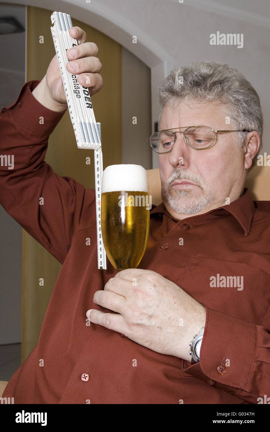 Man checked with a ruler the level of the beer gla Stock Photo