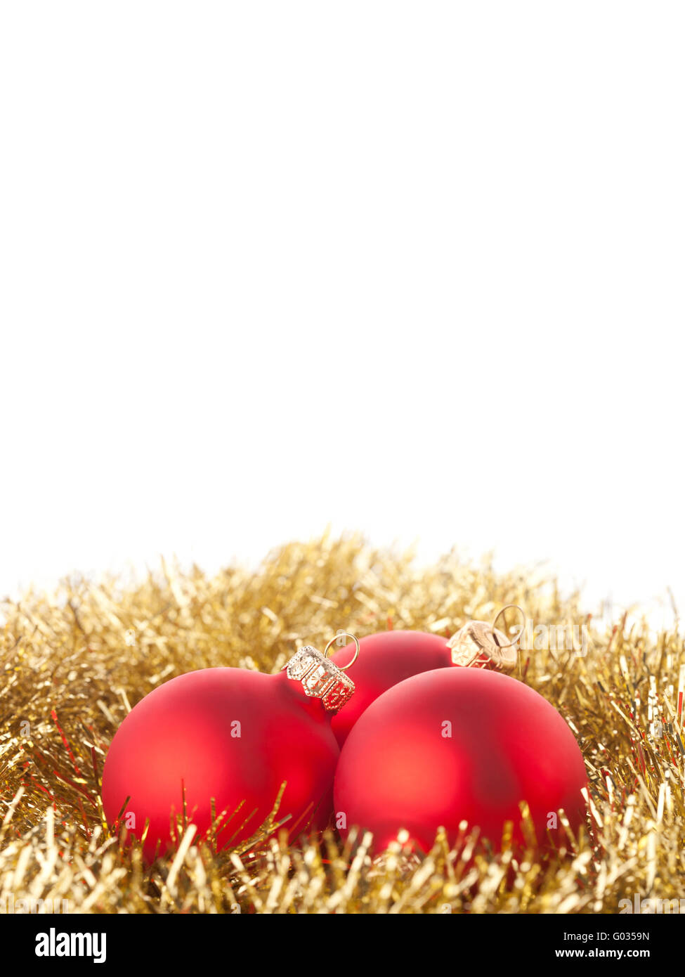 Red Christmas balls lying on a golden background - Stock Image