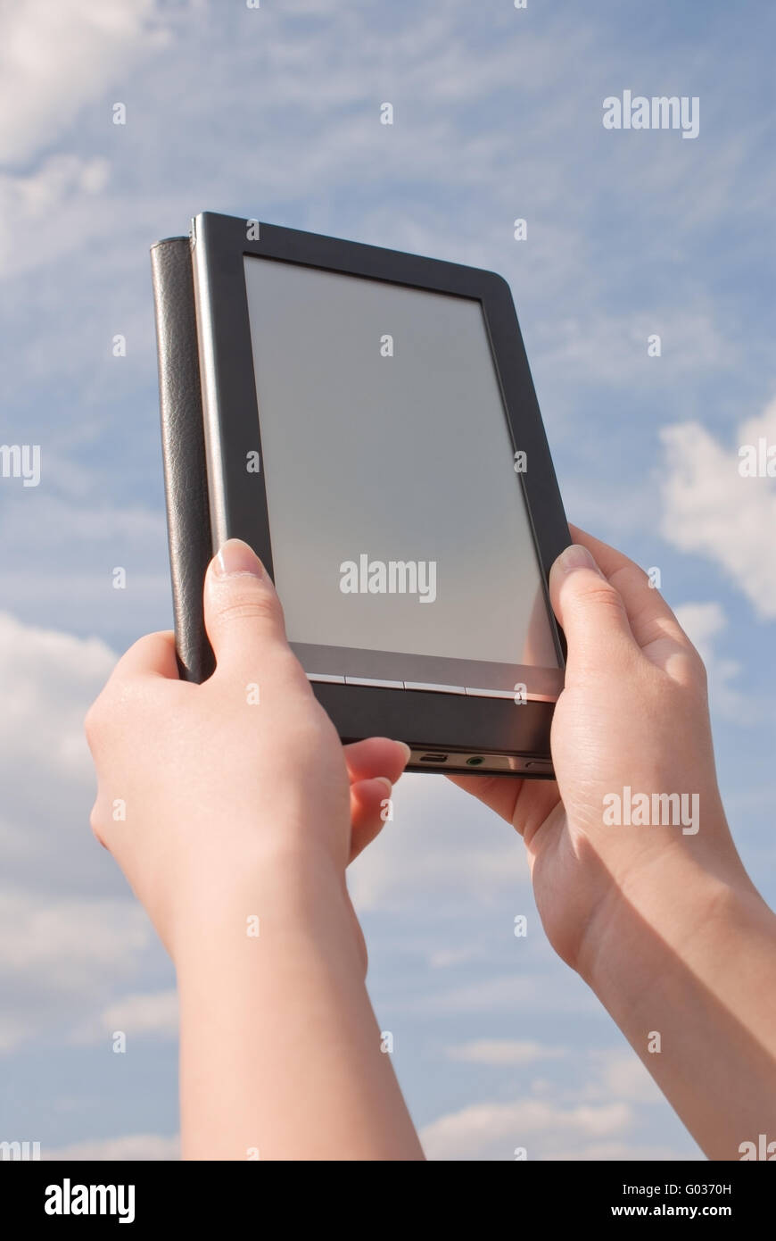 Hands hold electronic book reader against blue sky - Stock Image