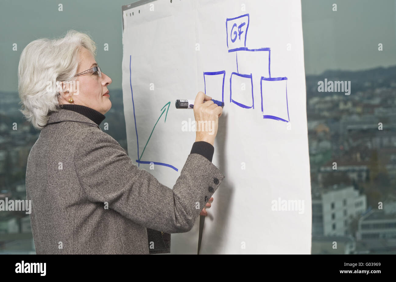 Senior Business woman writing on a whitewall - Stock Image