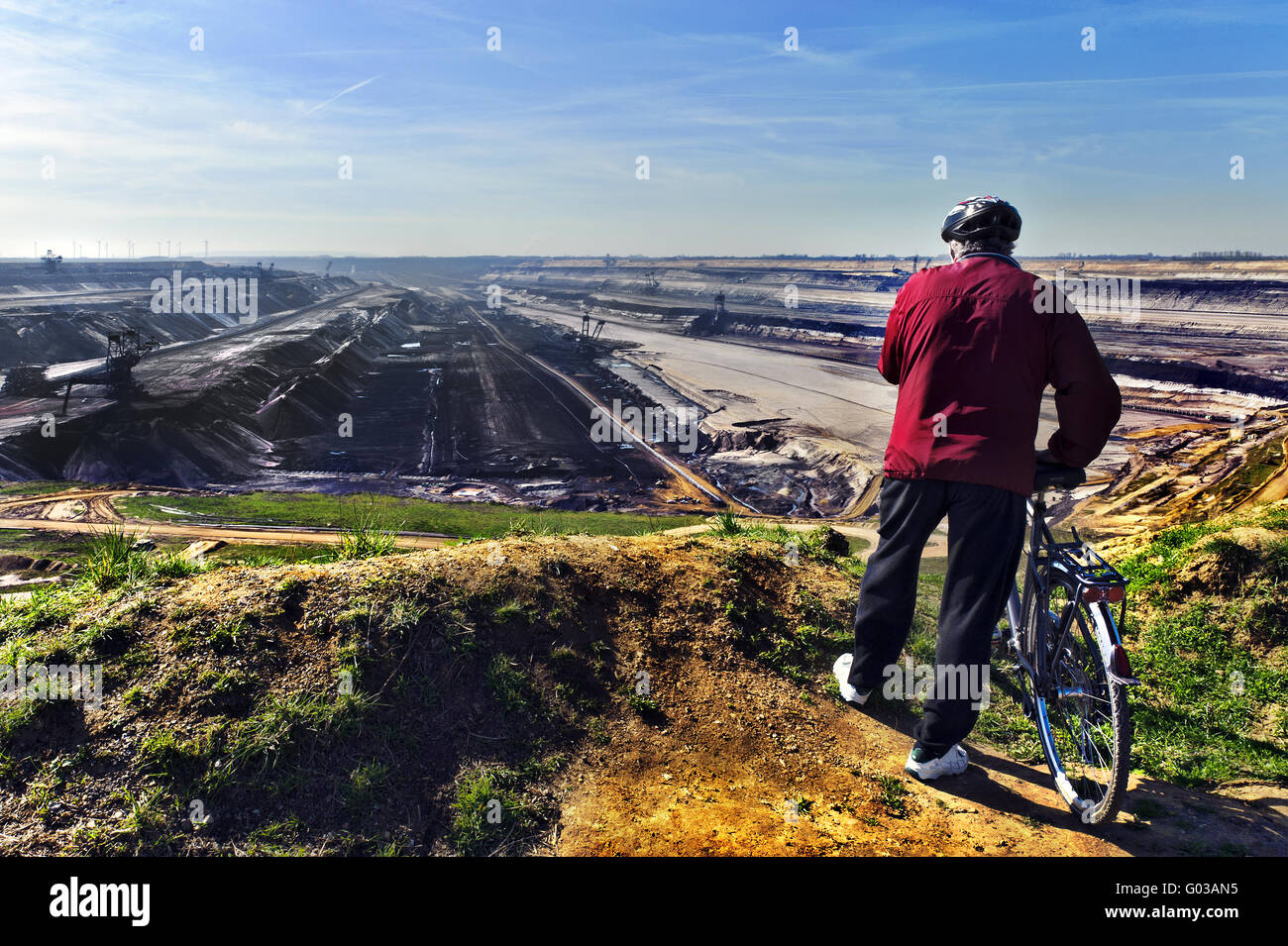 Man with bicycle stands at the edge of a pit mine - Stock Image