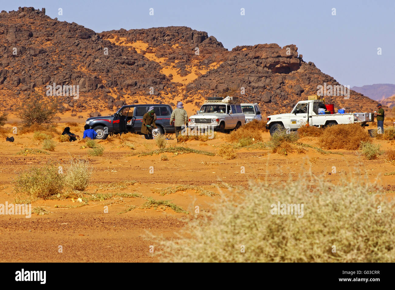 Off-road vehicles at a meeting point in the desert - Stock Image