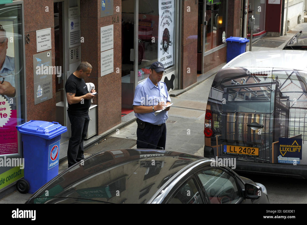 Traffic warden issueing a parking ticket,Luxemboug - Stock Image