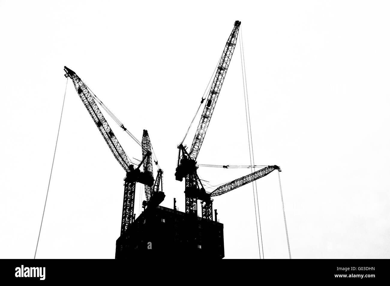 Black and white silhouette crane on top an under construction  building - Stock Image