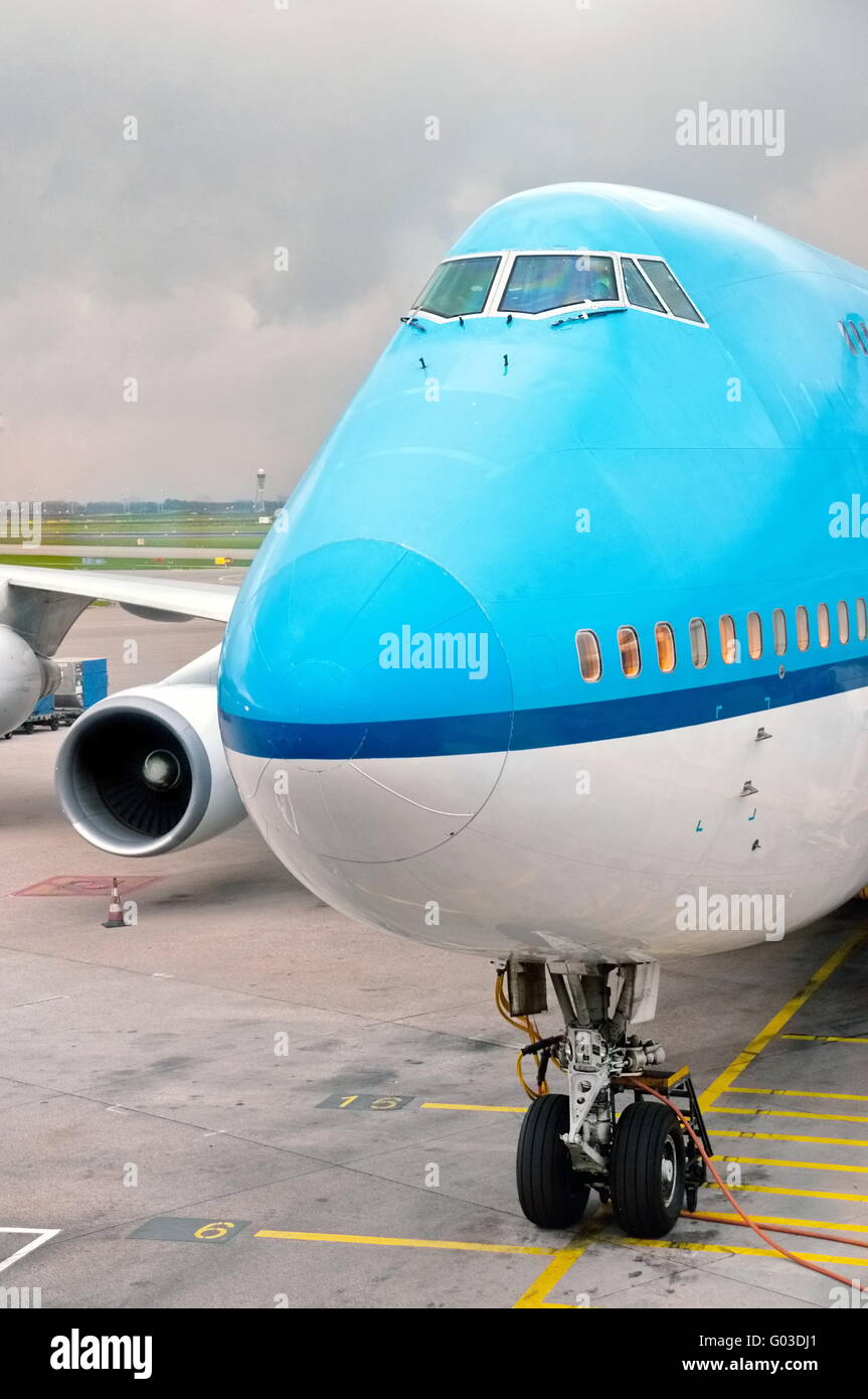 Blue and white landed aircraft docked in airport - Stock Image