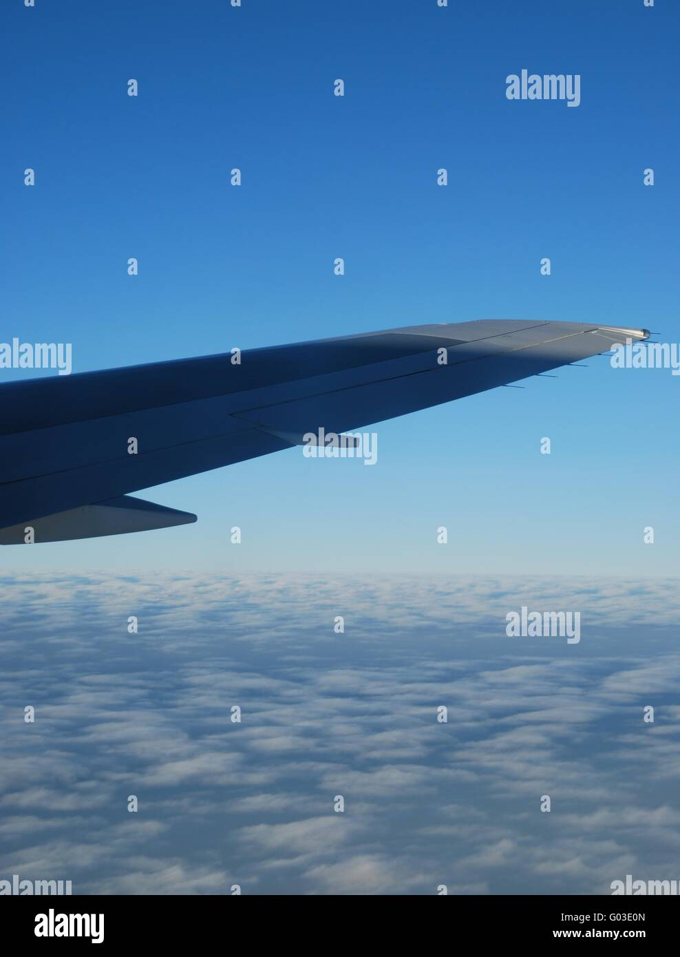 photo of a airplane wing and clouscape scene - Stock Image