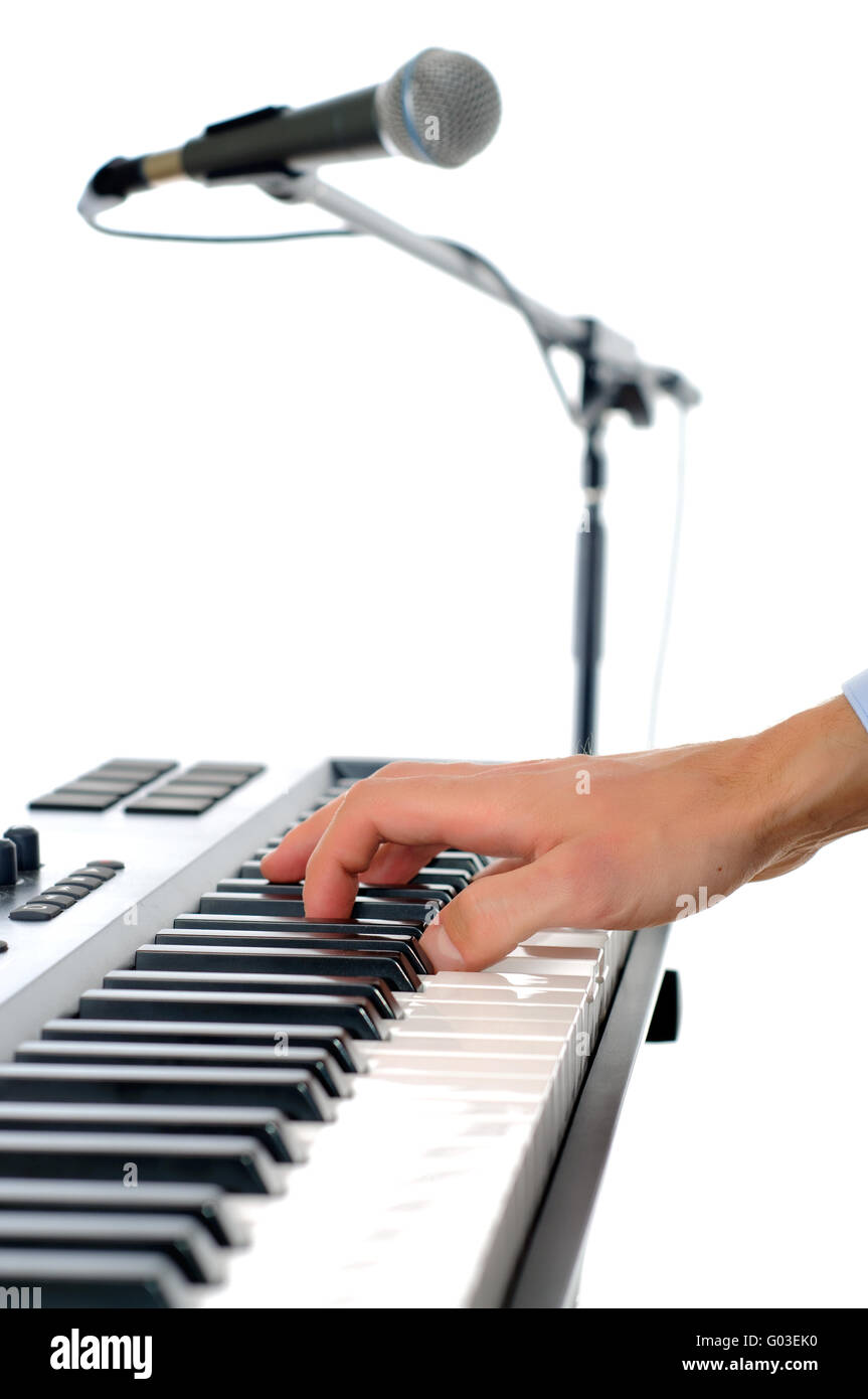 maicrophone and male hands playing the piano in the studio isolated on white - shallow pepth of firld with focus - Stock Image