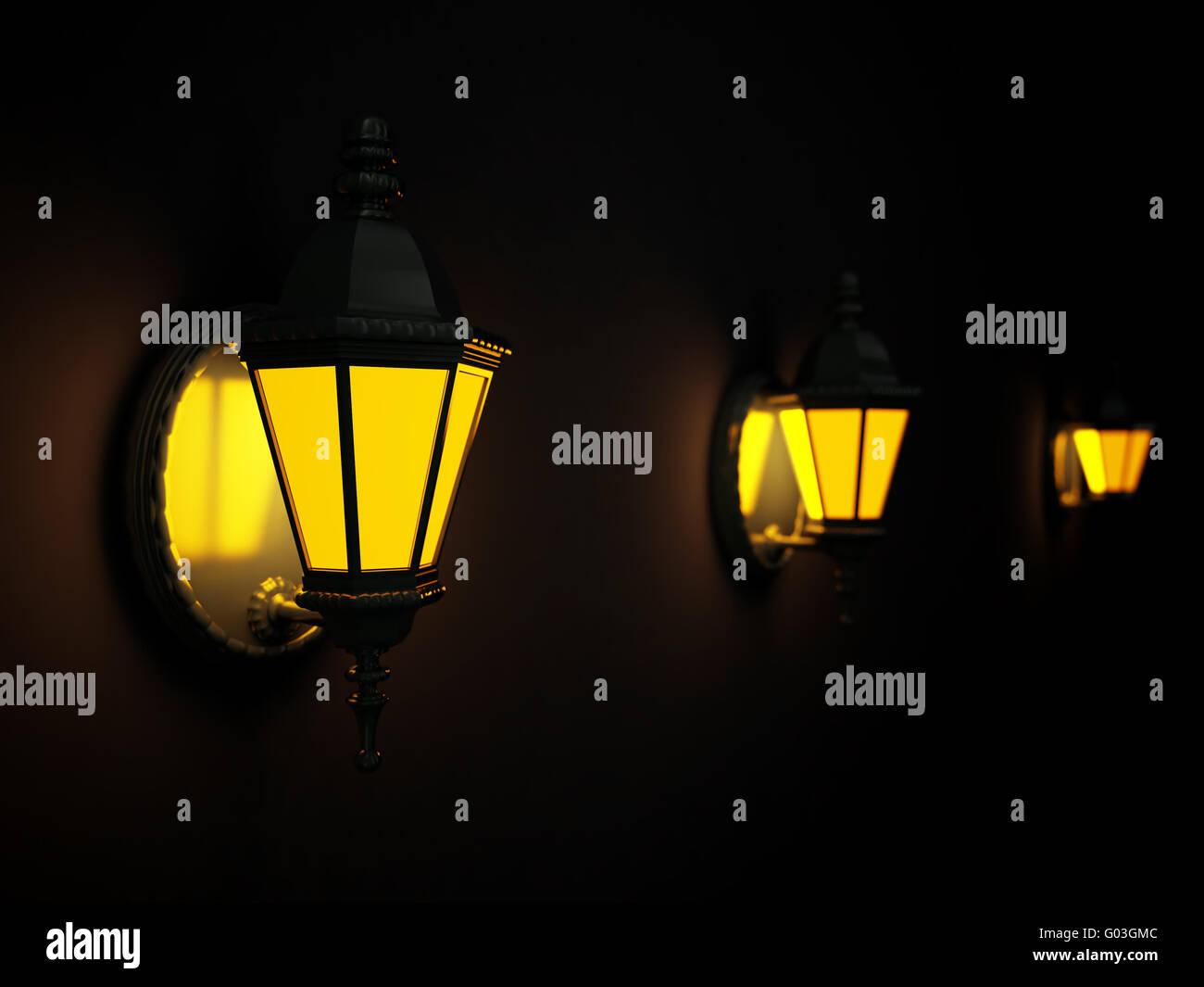 Shone street lanterns on a wall at dark night - Stock Image