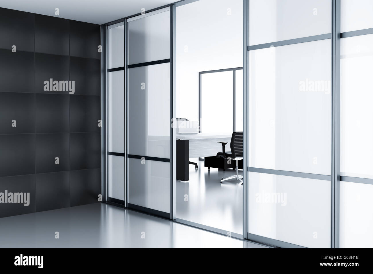 Empty cubicle with laptop on table behind a glass - Stock Image