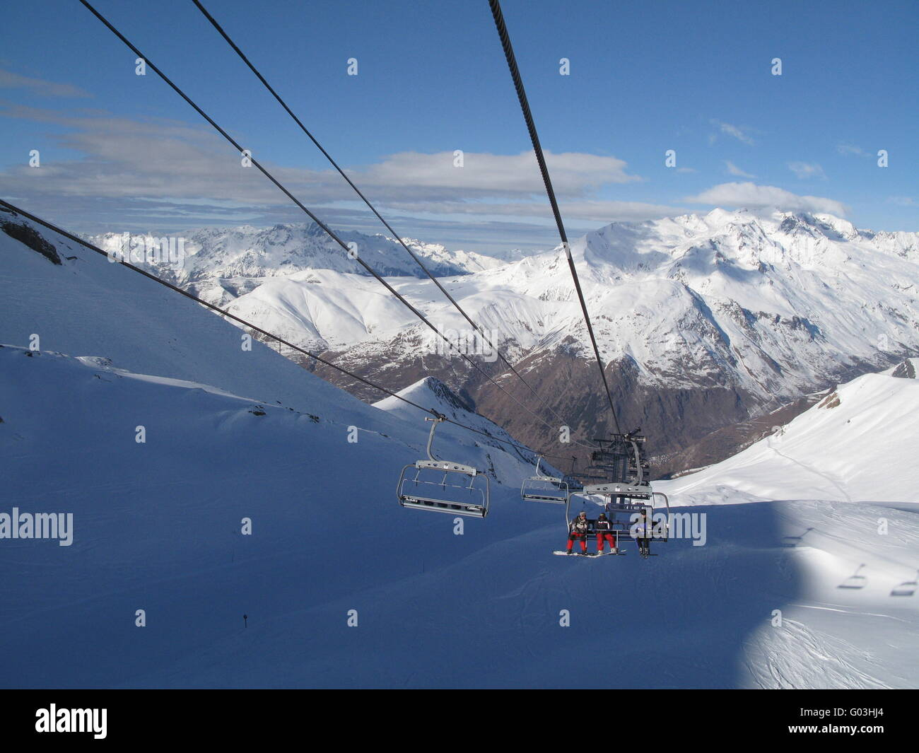 sunny alpine scene with chairlifts Stock Photo