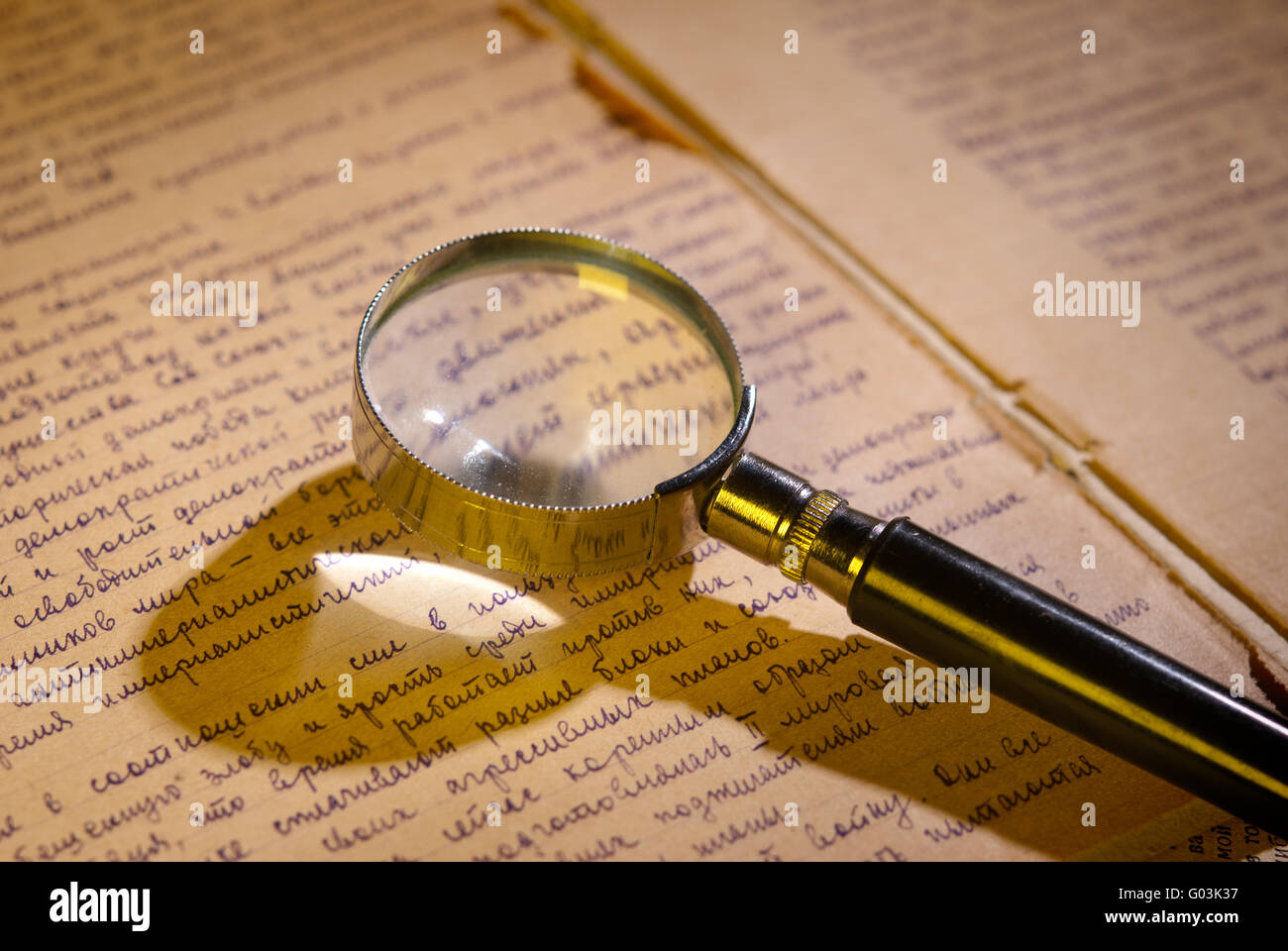 Magnifier glass on page of ancient manuscript - Stock Image