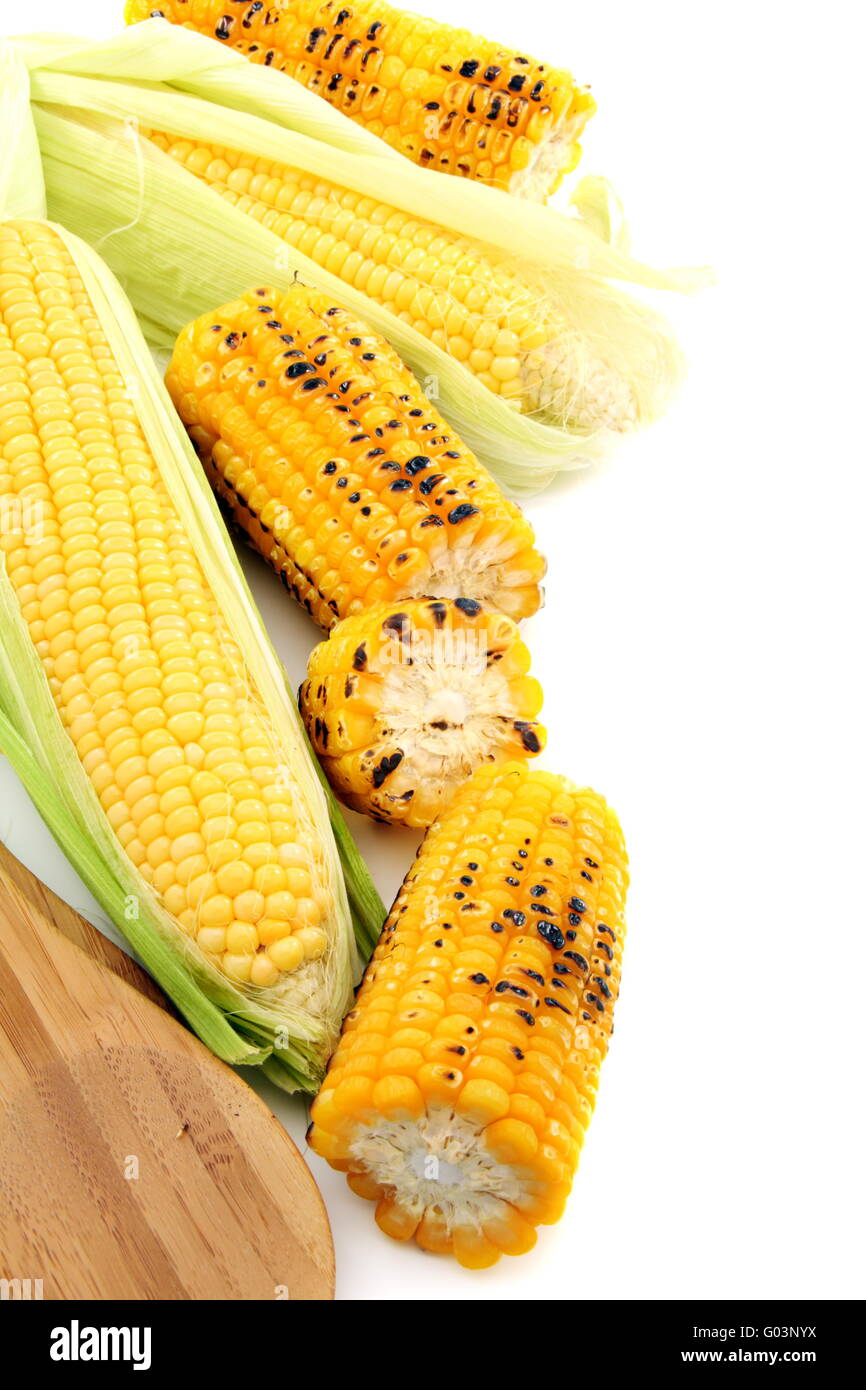 Cleaning freshly roasted ears of corn on cob with green leaves. - Stock Image