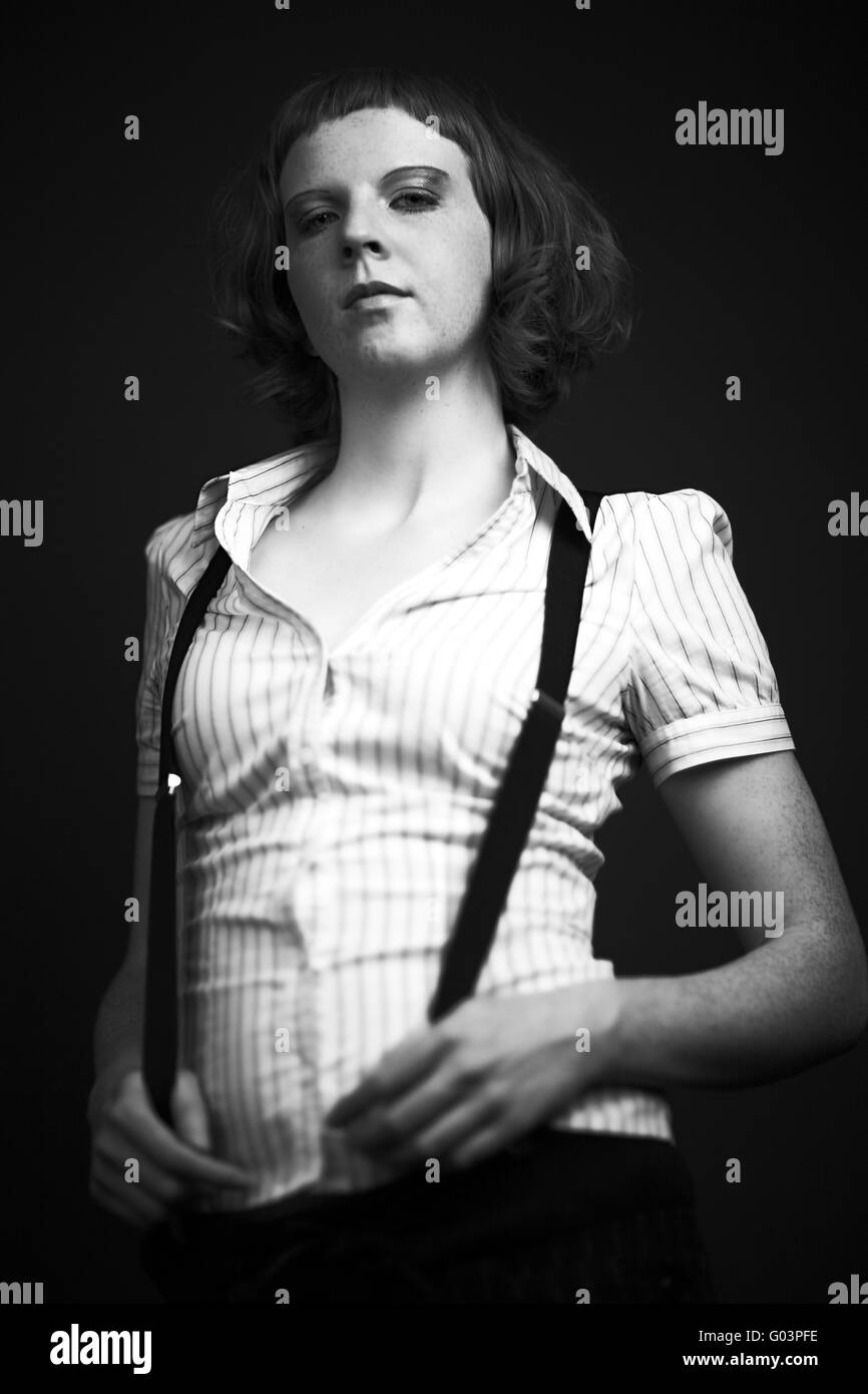 Young woman in 20s style on a black background - Stock Image
