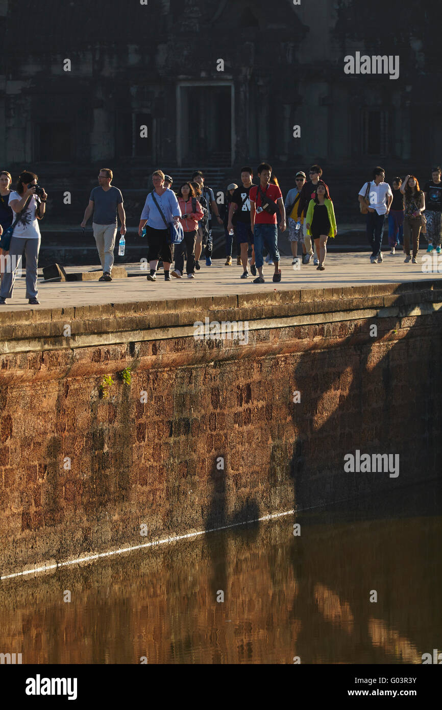 Tourists on ancient sandstone causeway crossing the moat to Angkor Wat (12th century), Angkor World Heritage Site, - Stock Image