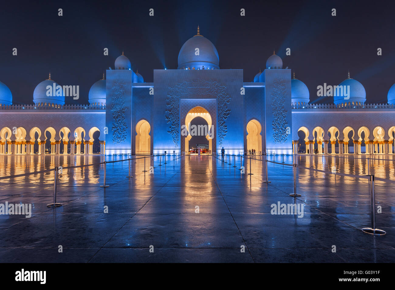 Sheikh Zayed Grand Mosque at Night Covered with Beautiful Blue Lights and light rays Stock Photo