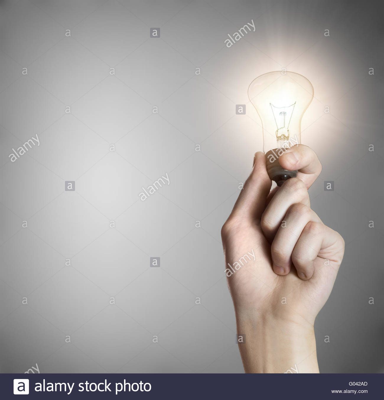 Glowing lightbulb in a hand on gray background with copyspace - Stock Image