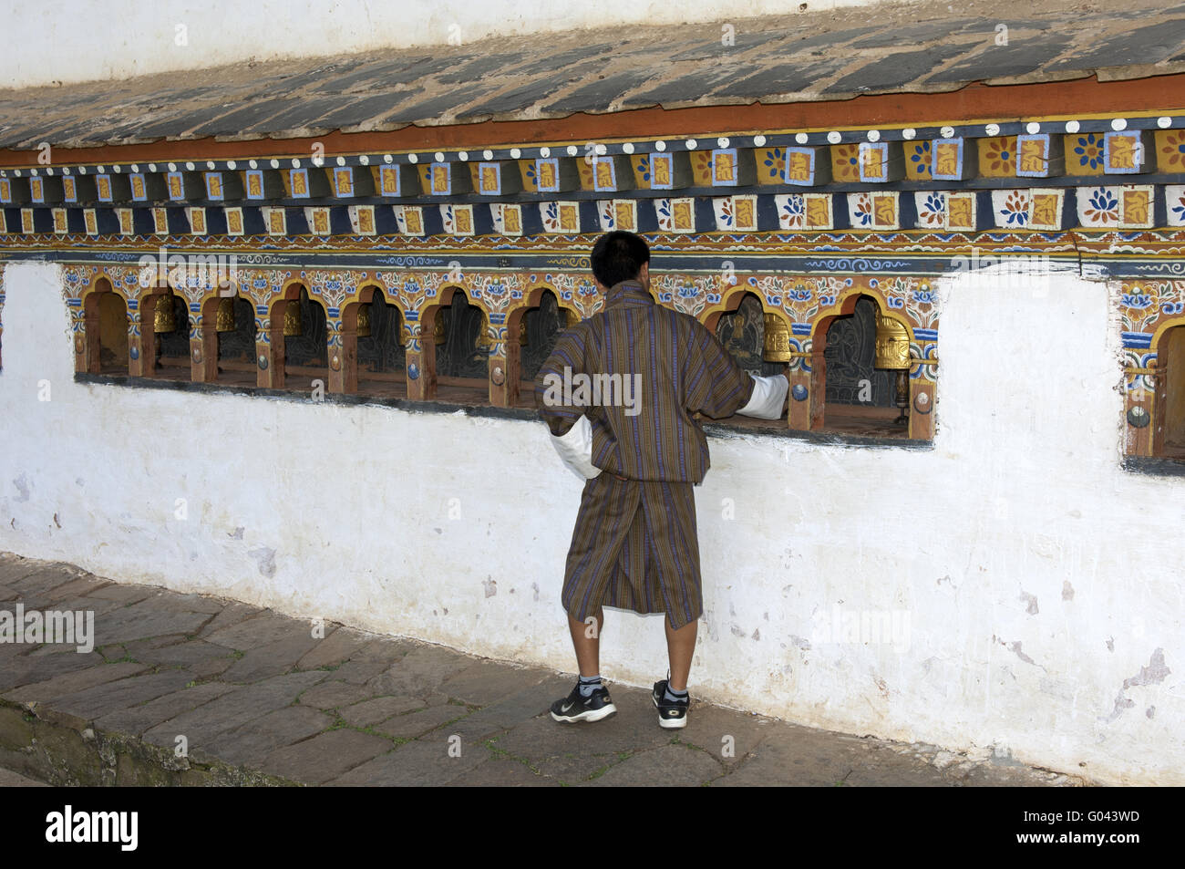 Bhutanese man at a prayer mill in the Temple - Stock Image
