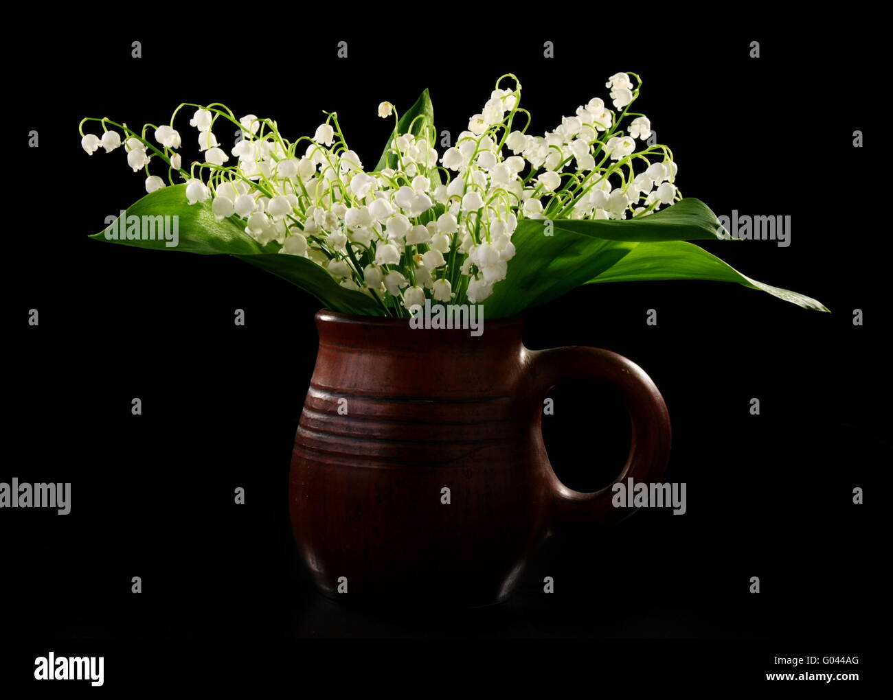 Bouquet lilies of the valley in a ceramic mug. - Stock Image