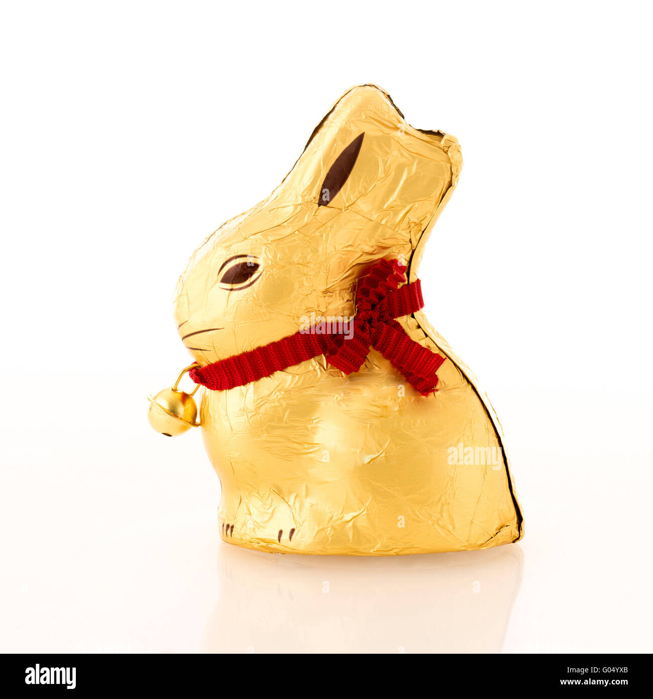 Chocolate gold foil wrapped rabbit against white background. - Stock Image