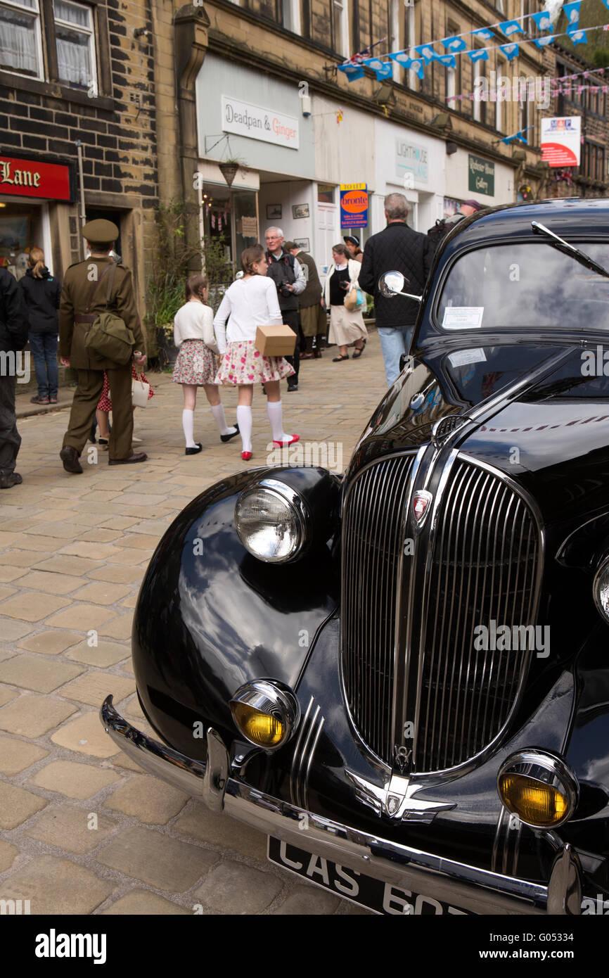 UK, England, Yorkshire, Haworth 40s Weekend, Main Street, visitors passing American Plymouth motor car - Stock Image