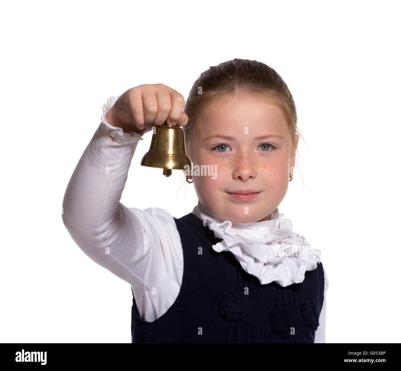 Young school girl ringing a golden bell on white background - Stock Image