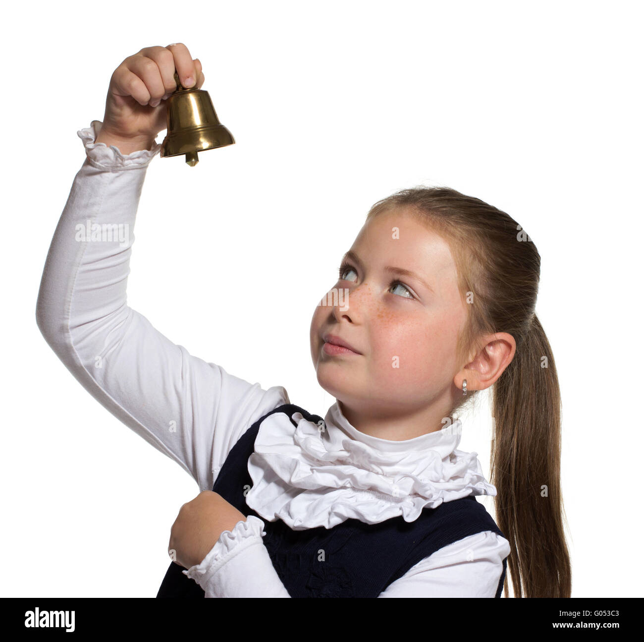 Young school girl looking to golden bell on white background - Stock Image
