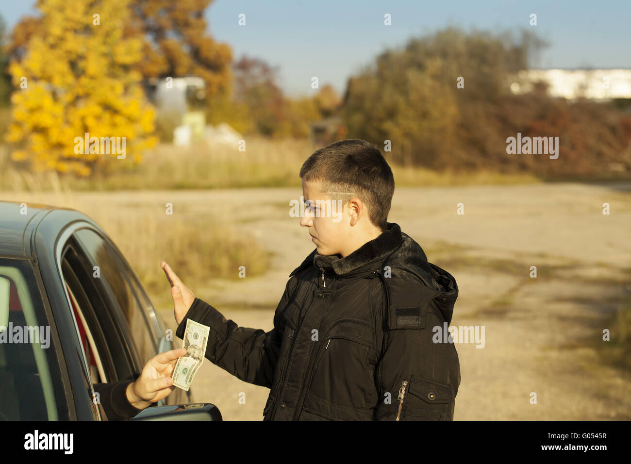 Someone from the car is offering money to the boy - Stock Image