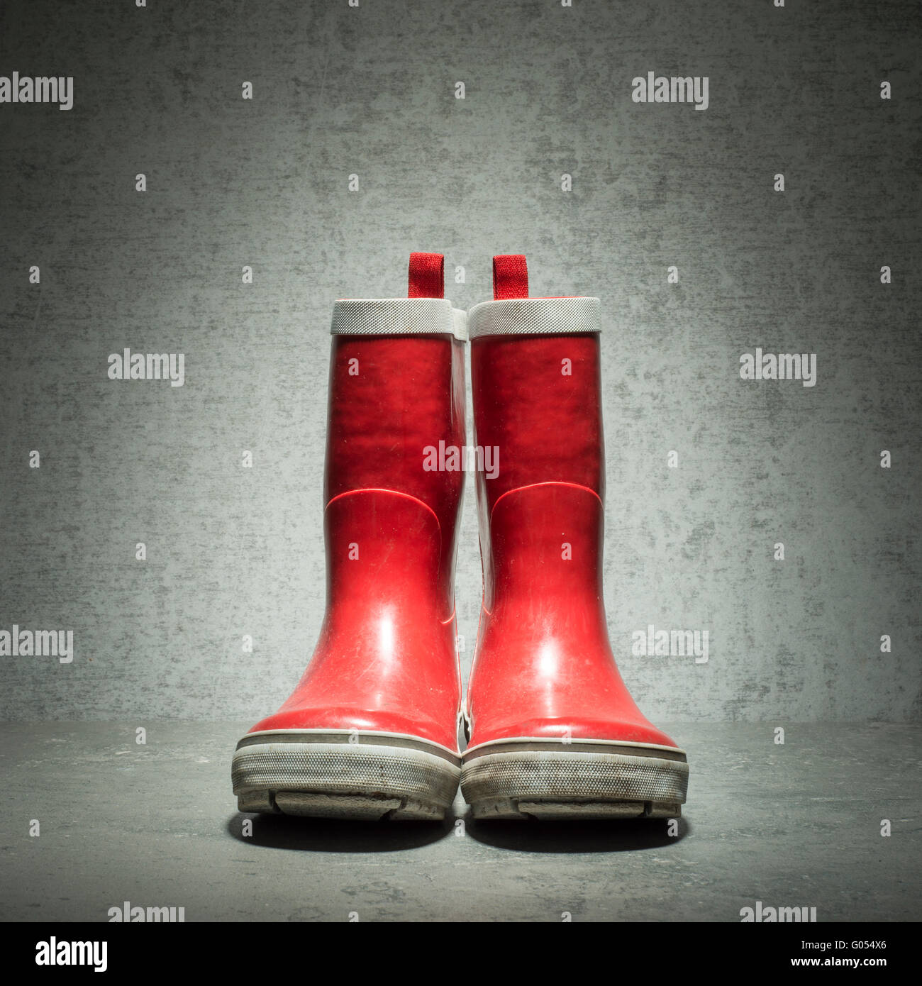 Red rubber boots in front of stone wall. Still life showing used waterproof rainboots. - Stock Image