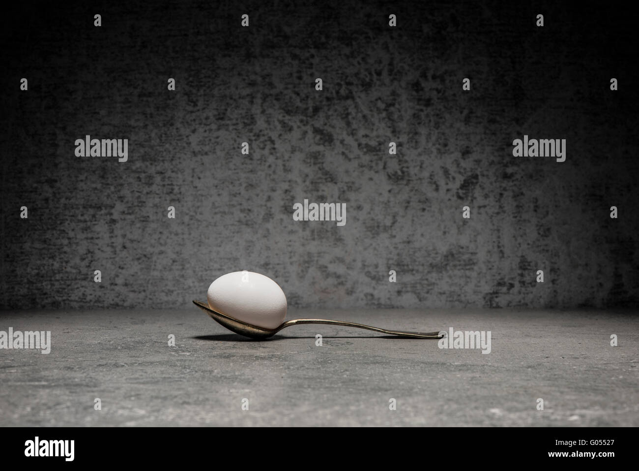 Egg and spoon still life. Conceptual image with simplicity and copy space. - Stock Image