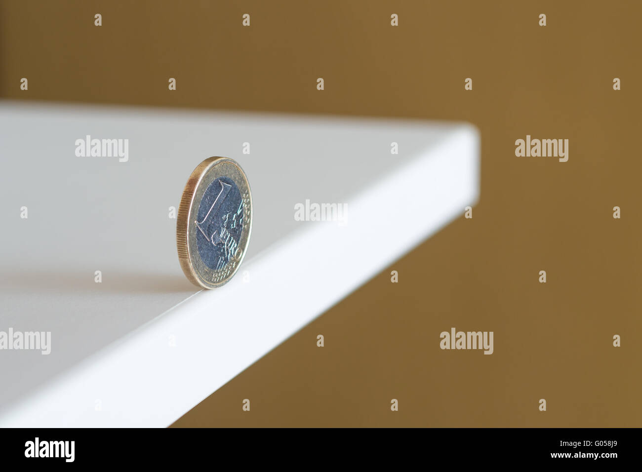 Euro rolls along the edge of the table - Stock Image
