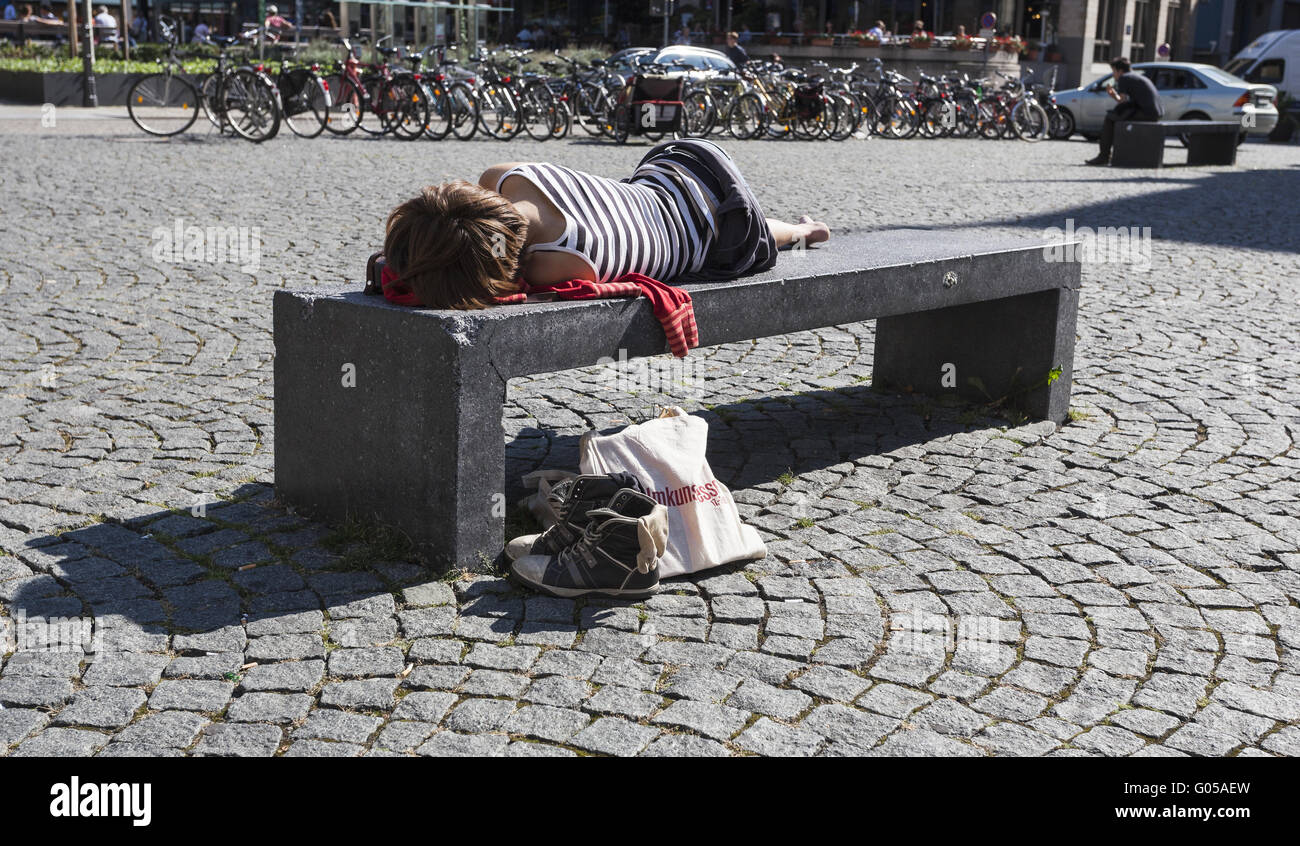 young woman sleeping on hard stone bench in the ci - Stock Image